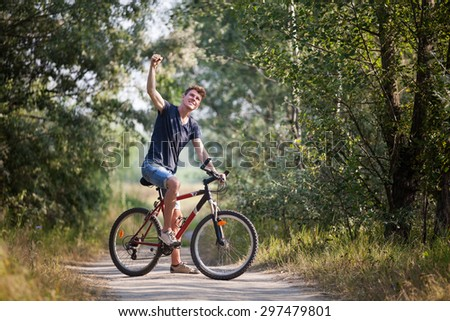 Man on the bicycle, winning gesture - stock photo
