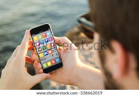 man on the coast using his smartphone. All screen graphics are made up. - stock photo