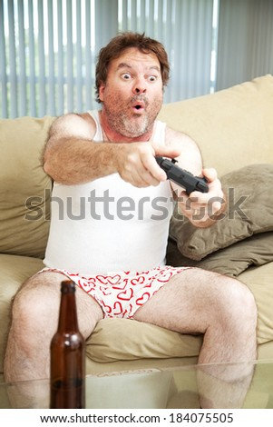 Man on the couch playing a video game in his underwear. Beer bottle in foreground.   - stock photo
