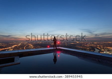 man on the edge of the roof of a skyscraper at night - stock photo