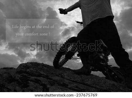 man on the edge on rock with dirt bike, unknown inspirational quote above - stock photo