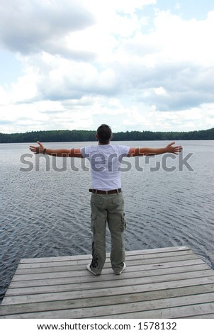 Man on the end of a pier expressing happiness and freedom - stock photo