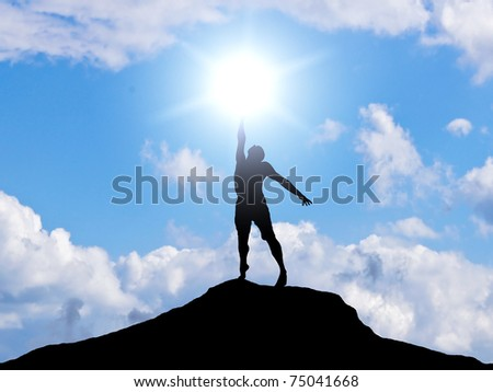 man on the mountain reaches for the sun - stock photo