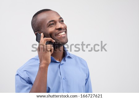 Man on the phone. Cheerful black man talking on the mobile phone and smiling while standing isolated on grey - stock photo