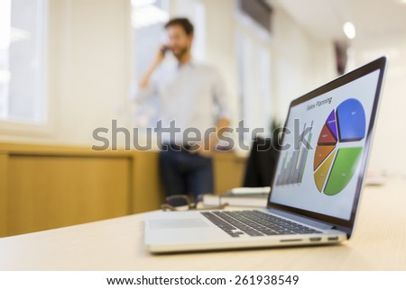 Man on the phone in office, laptop in the foreground - stock photo