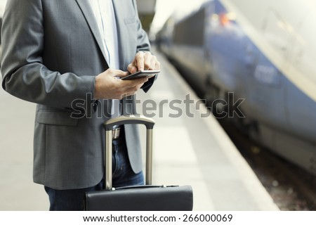 Man on the platform station. Typing text message on mobile phone - stock photo