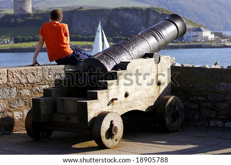 man on the rampart with old cannon, Plymouth, UK - stock photo