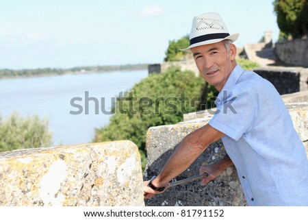 Man on the ramparts overlooking the river - stock photo