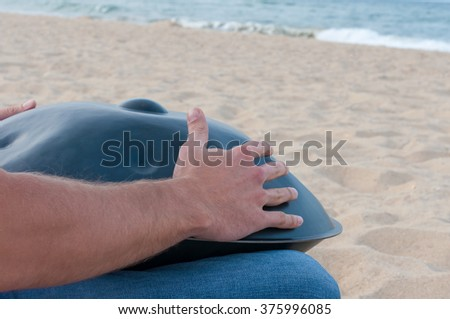 Man on the sand beach playing handpan or hang with sea On Background. The Hang is traditional ethnic drum musical instrument - stock photo