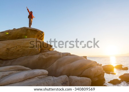Man on the sheer cliff - stock photo