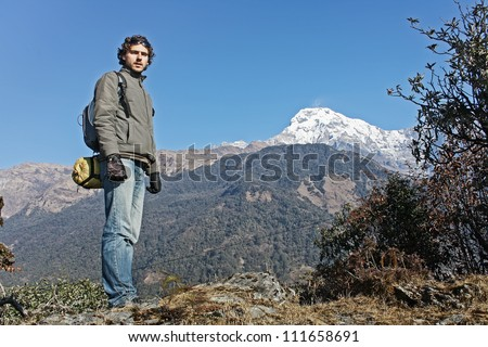 Man on the top. A portrait of a man over Annapurna South glacier. - stock photo