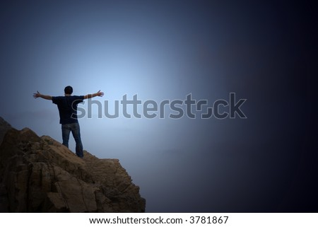 man on the top of a cliff with open arms