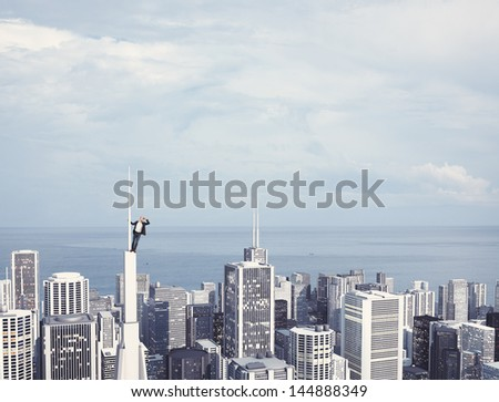 man on the top of skyscraper looking at the city - stock photo