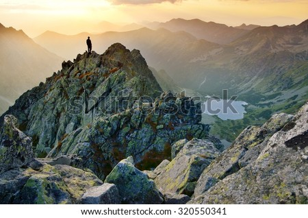 Man on the top of the hill watching wonderful scenery in mountains during summer colorful sunset in High Tatras in Slovakia - stock photo