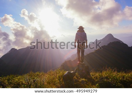 Man on the top of the hill watching wonderful scenery in mountains during sunset time, Successful and alone concept.