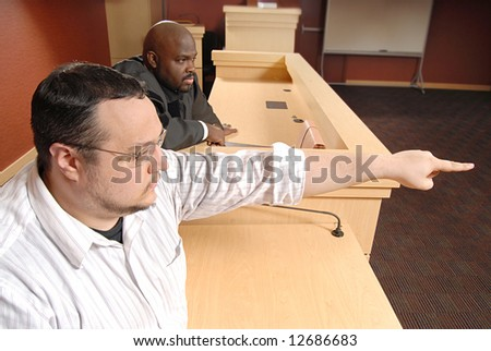 Man on the witness stand pointing out someone to the judge - stock photo