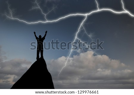man on top of a mountain in the sky with bright lightning - stock photo