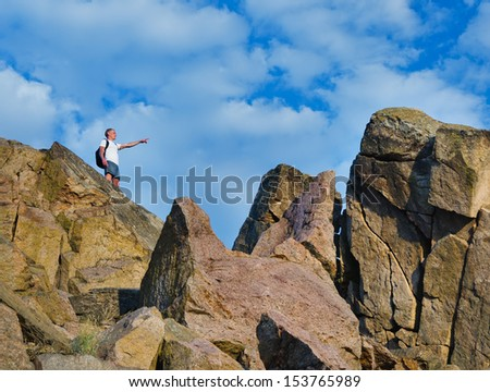 Man on top of a rocky mountain cliff pointing with his arm towards a higher peak ahead of him indicating that he is going to attempt to climb up to it