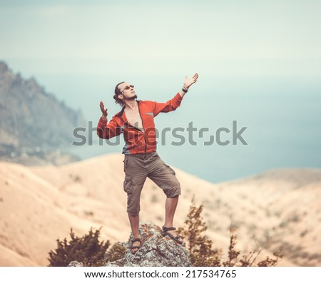 Man on top of mountain holding arms up - stock photo