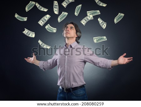 Man on top of the money roll in and he catches them. - stock photo