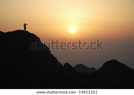 Man on top of the mountain during sunset. - stock photo