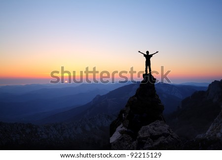 man on top of the mountain looking to the sun - stock photo