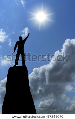 man on top of the mountain reaches for the moon - stock photo