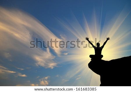 man on top of the mountain reaching for the sun - stock photo