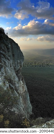 man on top of the rock - stock photo