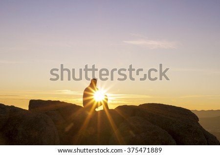 Man on top watching the sunset alone