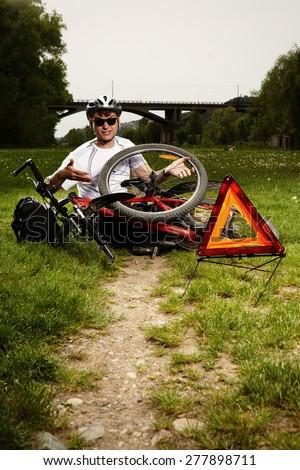Man on trip fixing broken bicycle - stock photo