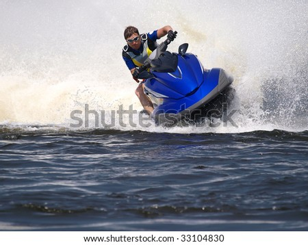 Man on Wave Runner rides fast with much splashes - stock photo