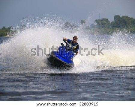 Man on Wave Runner rides very fast with much splashes - stock photo