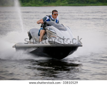 Man on Wave Runner skims along very fast - stock photo