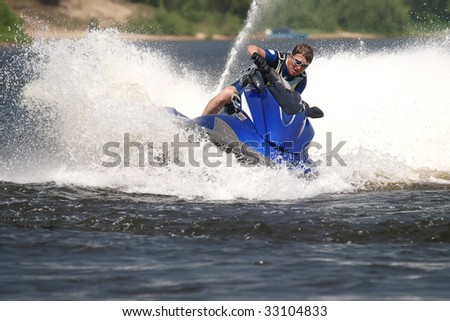 Man on Wave Runner turns fast with much splashes - stock photo
