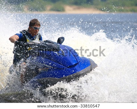Man on Wave Runner turns very fast with diving - stock photo