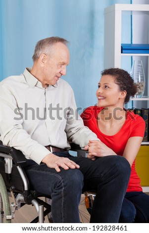 Man on wheelchair and his guardian, vertical - stock photo