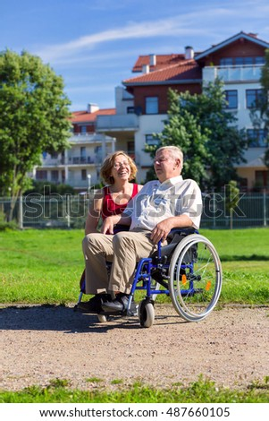 man on wheelchair with optimistic young woman in the park