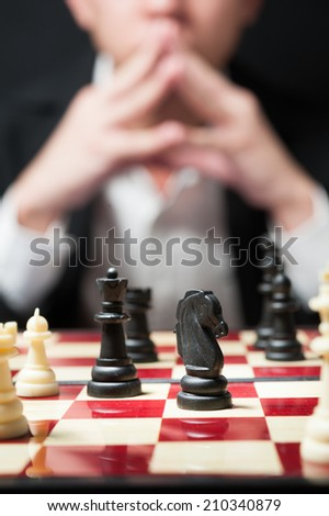 Man on white shirt black suit playing chess think for strategy business concept - stock photo