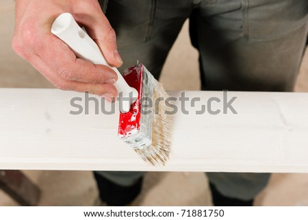 Man � only hands to be seen -  is painting in his house; presumably he is renovating - stock photo