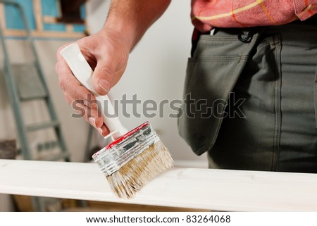 Man - only hands to be seen -  is painting in his house; presumably he is renovating - stock photo