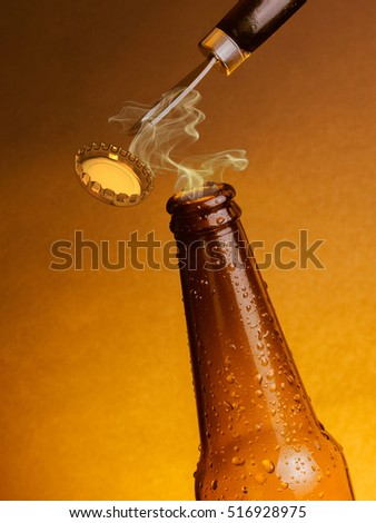 man open fresh cold beer ale bottles with drops and stopper open with bottle opener on warm background