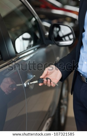 Man opening a car with a key in a car dealership