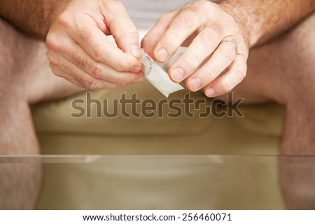 Man opening a gram of cocaine and getting ready to pour it on a glass coffee table.  