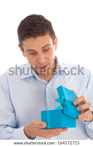 Man opening a surprise gift in a colourful turquoise blue box decorated with a bow with a look of joyful anticipation as he celebrates Christmas or his birthday