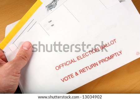 Man opening ballot he got in the mail - stock photo