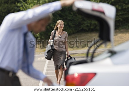 Man opening car boot in car park, focus on businesswoman walking with luggage in background, smiling - stock photo