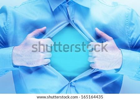 Man opening his blue shirt - stock photo