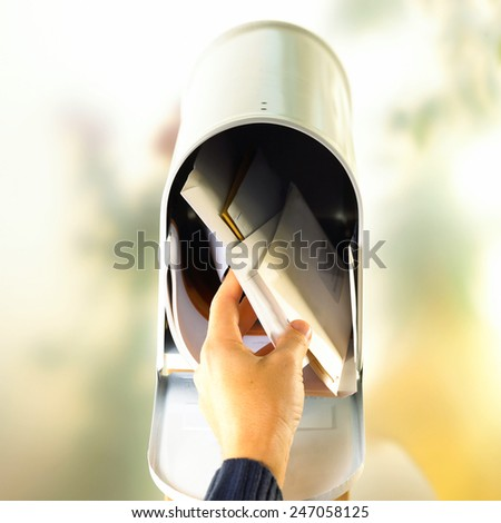 Man opening his mailbox to remove mail inside - stock photo