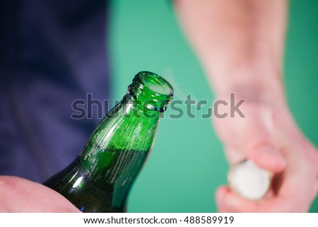 man opens a bottle of beer in studio